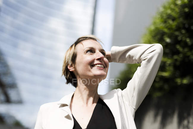 Smiling businesswoman looking up against office building — Stock Photo