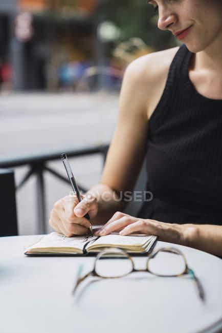 Nahaufnahme einer jungen Frau, die im Café sitzt und Notizen in Notizbuch schreibt — Stockfoto