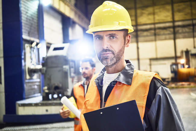 Portrait of confident man wearing protective workwear in factory — Stock Photo