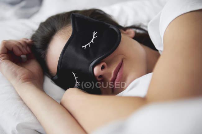 Porträt einer jungen Frau mit Schlafmaske im Bett — Stockfoto