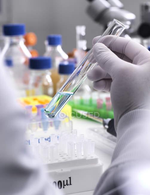 Forschungsexperiment, bei dem Wissenschaftler eine chemische Formel in einem Reagenzglas mischen — Stockfoto