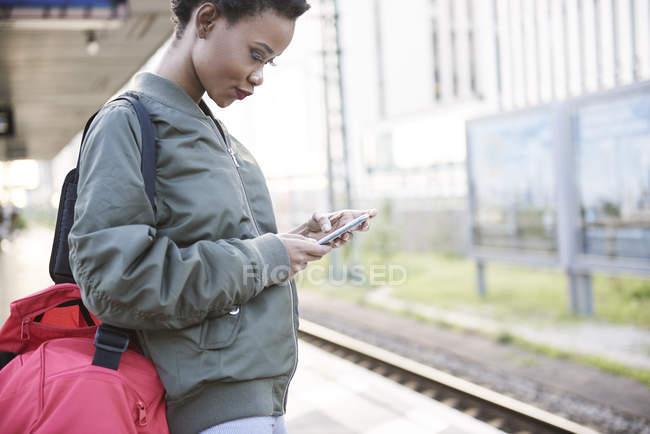 Giovane donna in piedi sulla piattaforma guardando il telefono cellulare — Foto stock
