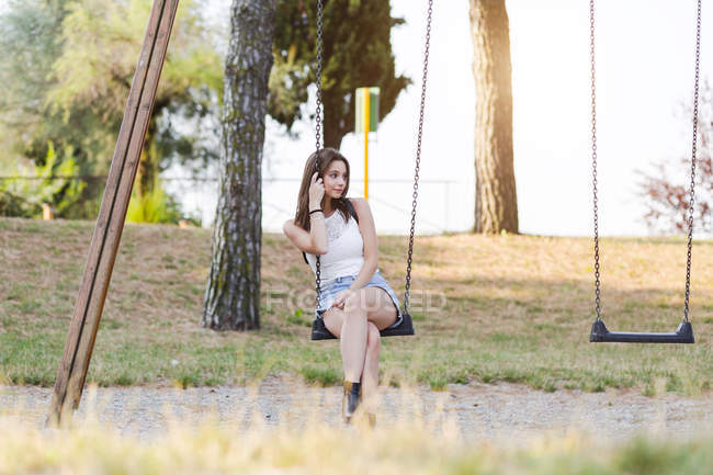 Young woman sitting on a swing on a playground — Stock Photo