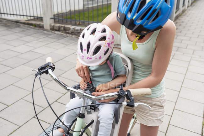 Мать и дочь катаются на велосипеде, дочь в шлеме, сидявом в детском кресле, пристегнув ремень безопасности — стоковое фото