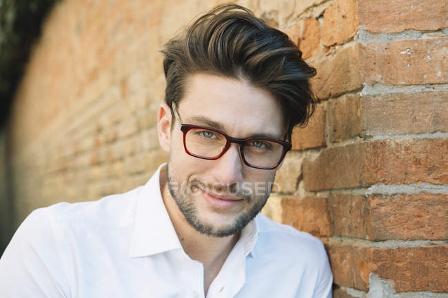 Portrait of a smiling man wearing glasses at brick wall — Stock Photo