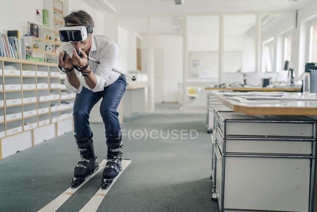 Бизнесмен катается на лыжах в офисе, используя очки VR — стоковое фото