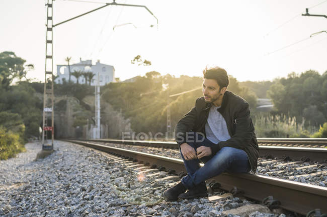 Young man sitting on railroad track — Stock Photo