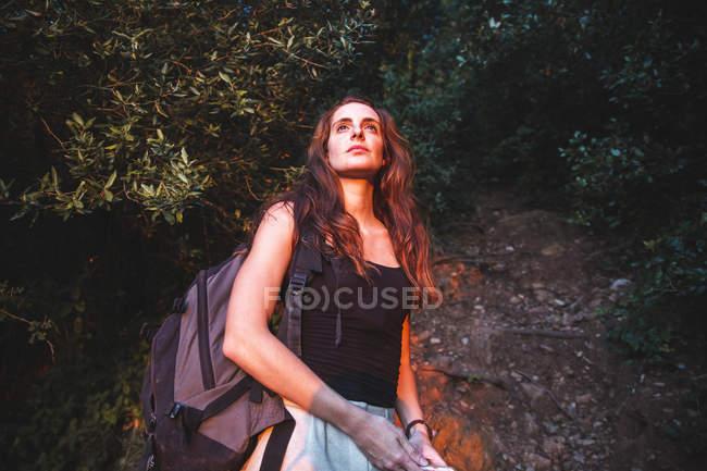Jeune femme sur un voyage de randonnée regardant autour — Photo de stock