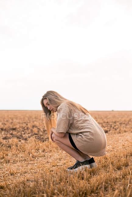 Jovem mulher agachado no campo — Fotografia de Stock
