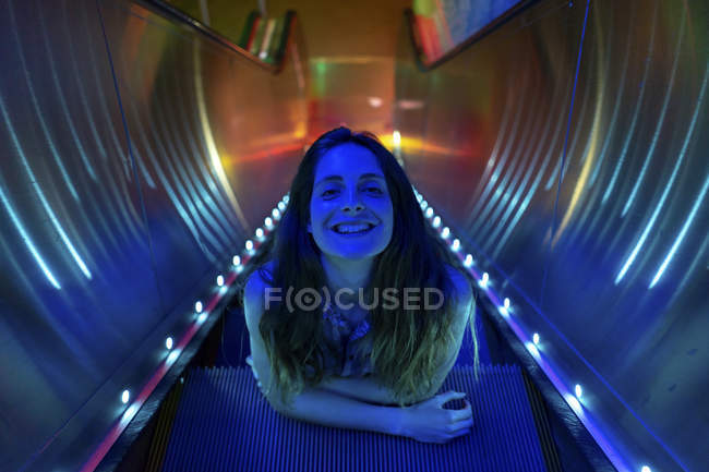 Portrait of blue illuminated young woman on steps of lighted escalator — Stock Photo