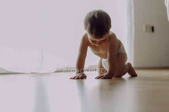 Curious little baby boy crawling on floor — Stock Photo