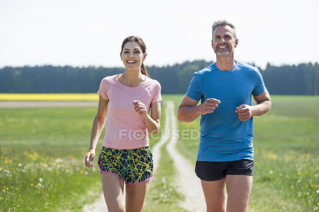 Casal correndo no caminho de campo — Fotografia de Stock