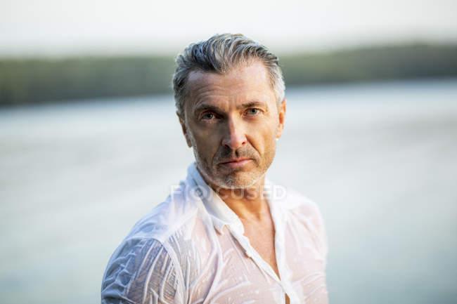 Portrait of mature man wearing wet white shirt at lake — Stock Photo