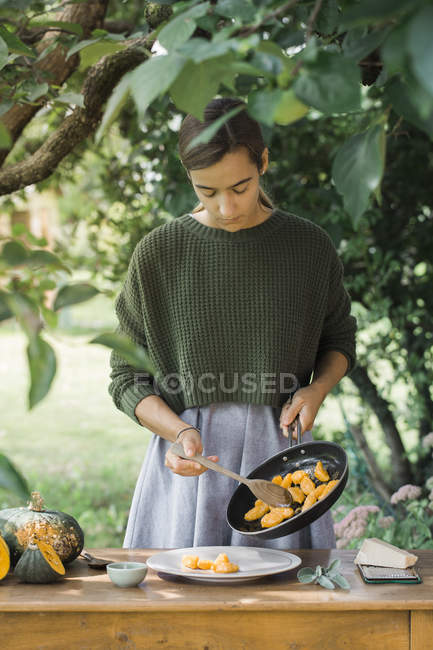 Молодая женщина с домашней тыквы gnocchis, приготовление пищи в кастрюле — стоковое фото