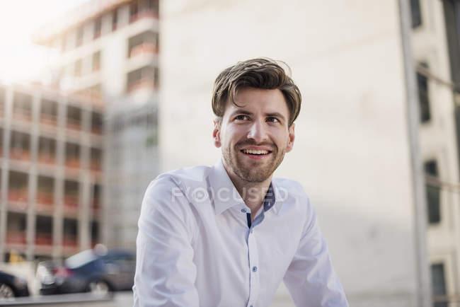 Porträt eines lächelnden Geschäftsmannes, der in der Stadt wegschaut — Stockfoto
