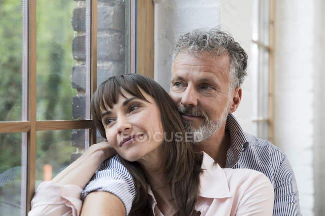 Доросла пара сидить на підвіконні, дивлячись у вікно. — стокове фото