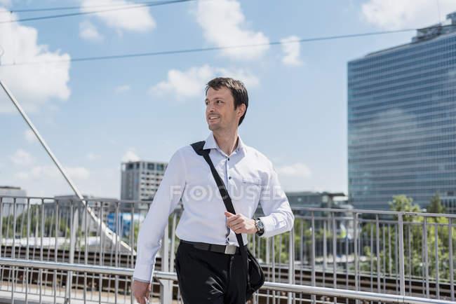 Lächelnder Geschäftsmann auf einer Brücke — Stockfoto