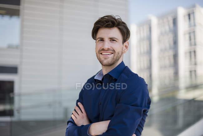 Portrait of confident businessman in city standing with arms crossed — Stock Photo