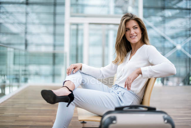 Smiling young businesswoman sitting outdoors with suitcase looking around — Stock Photo