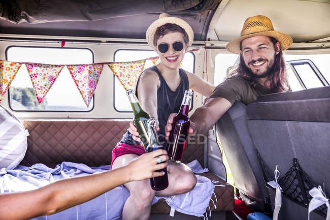 Счастливые друзья внутри фургона звенят бутылками — стоковое фото