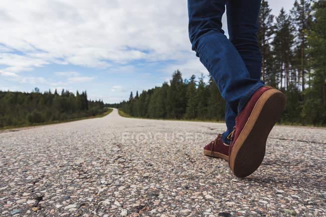 Неупереджений погляд людини на ноги, ноги людини, що йде по пустій сільській дорозі. — стокове фото