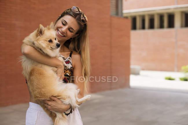 Souriant jeune femme tenant un chien dans la rue — Photo de stock