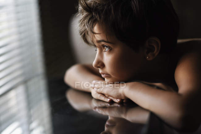 Portrait of little girl looking out of window in dark room — Stock Photo