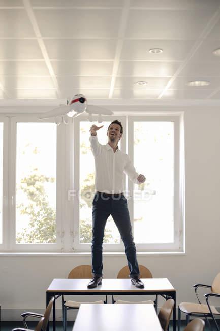 Empresário brincando com avião inflável no escritório — Fotografia de Stock