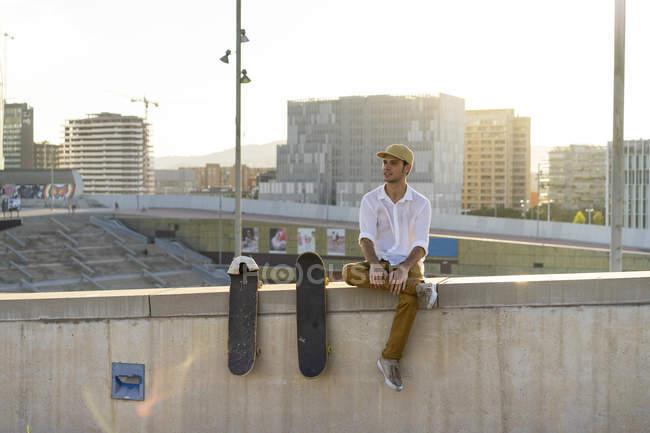 Junger Mann sitzt bei Sonnenuntergang auf Stadtmauer neben Skateboards — Stockfoto