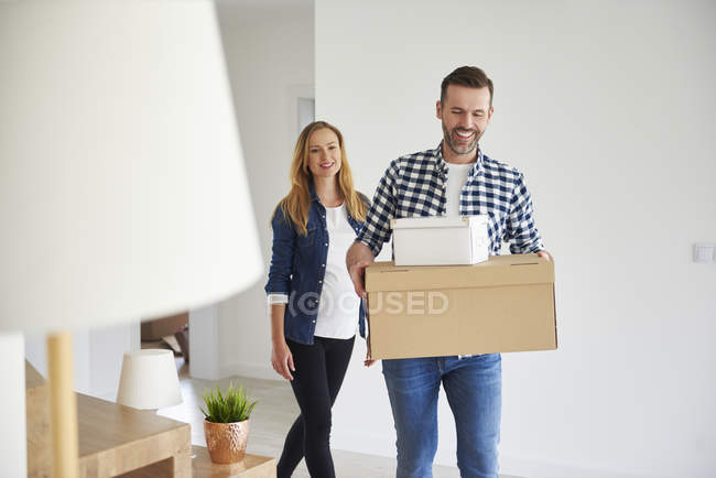 Happy couple moving into new flat carrying cardboard box — Stock Photo