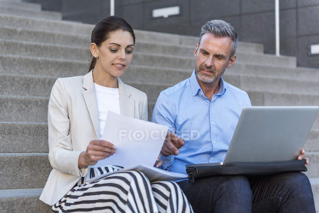 Two business people sitting side by side on stairs working together — Stockfoto