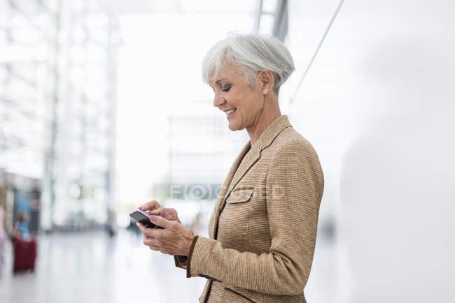 Smiling senior businesswoman using cell phone — Stock Photo