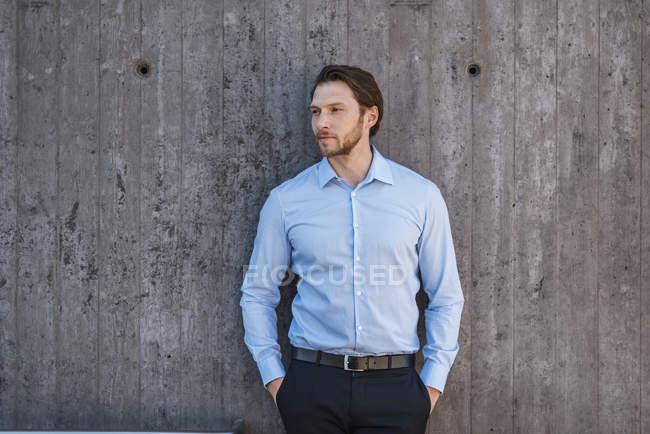 Ritratto di uomo d'affari in piedi al muro di cemento — Foto stock