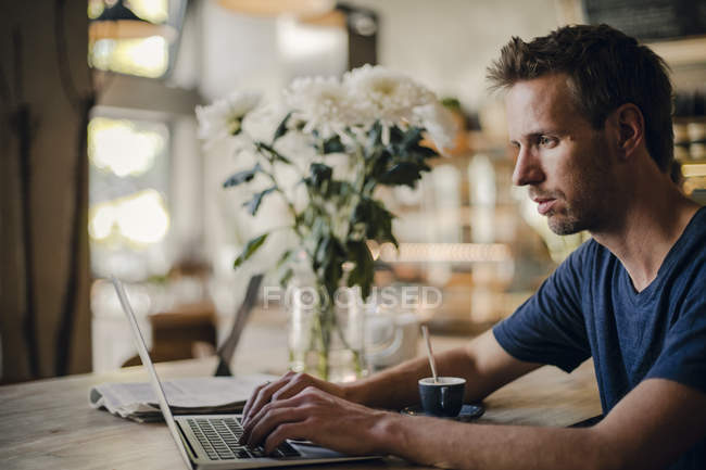 Mid adult man sitting in coffee shop, using laptop — Stock Photo