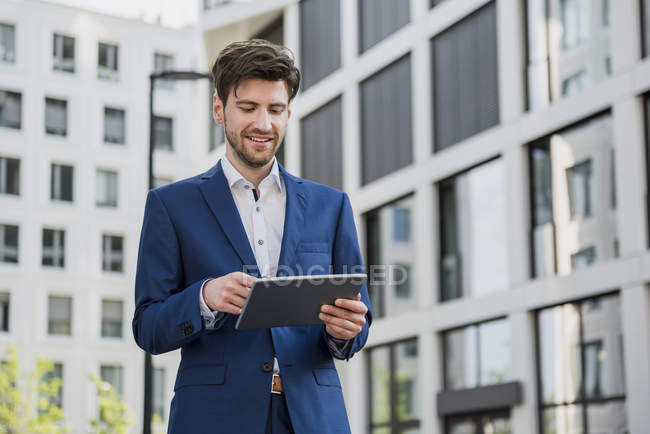 Smiling businessman in city using tablet — Stock Photo