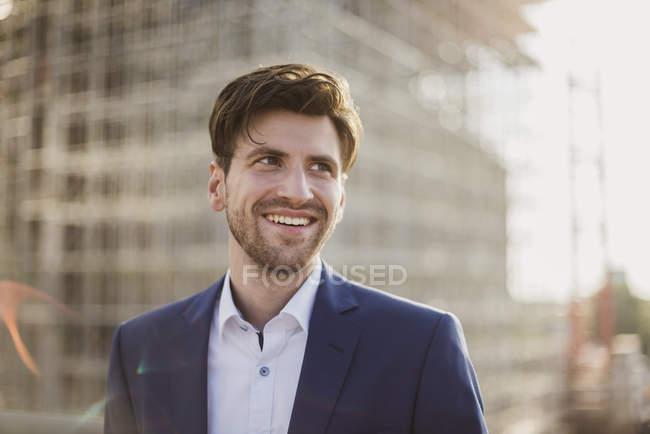 Porträt eines lächelnden Geschäftsmannes vor einer Baustelle mit seitlichem Blick — Stockfoto
