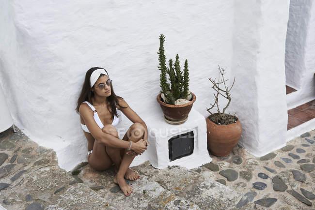 Пенсивная молодая женщина в белом бикини сидит на лестнице — стоковое фото