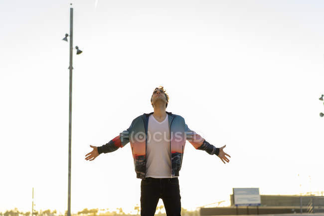 Man standing in the city with arms outstretched, looking up — Stock Photo