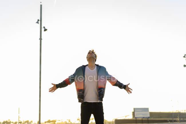 Equipe a posição na cidade com os braços outstretched, olhando acima — Fotografia de Stock