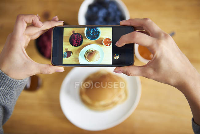 Young woman taking pictures of breakfast pancakes with berries and fresh fruit — Stock Photo