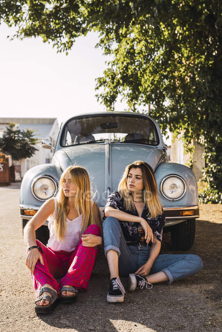 Two young women sitting outside at a vintage car — Stock Photo