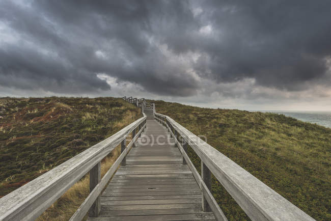 Germany, Schleswig-Holstein, Sylt, Wenningstedt, boardwalk to the beach under rain clouds — Stockfoto