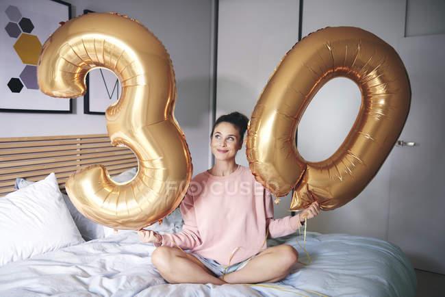 Счастливая женщина держит золотые воздушные шары на день рождения утром в постели — стоковое фото
