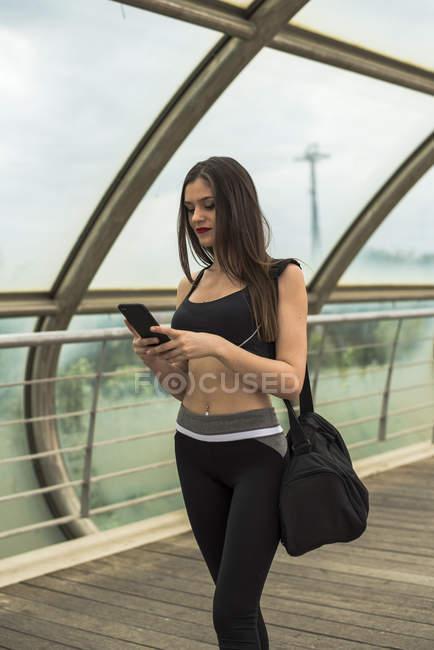 Спортивная женщина с помощью смартфона — стоковое фото