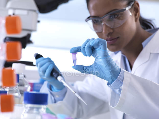 Genetic research, female scientist viewing sample in a eppendorf vial, analysis in the laboratory — Stock Photo