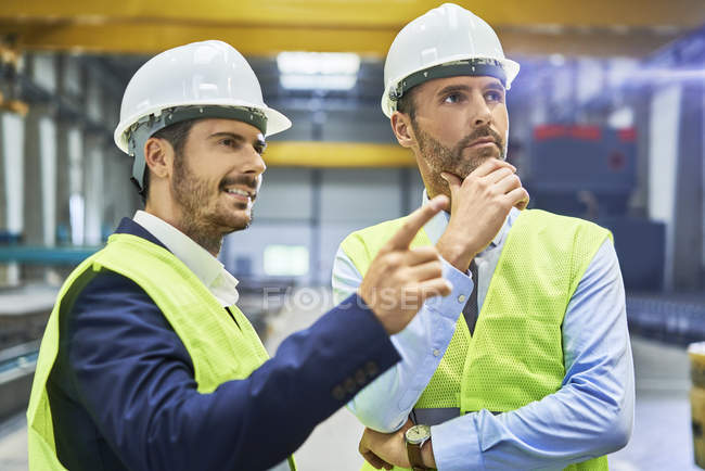Managers wearing protective workwear talking in factory — Stock Photo