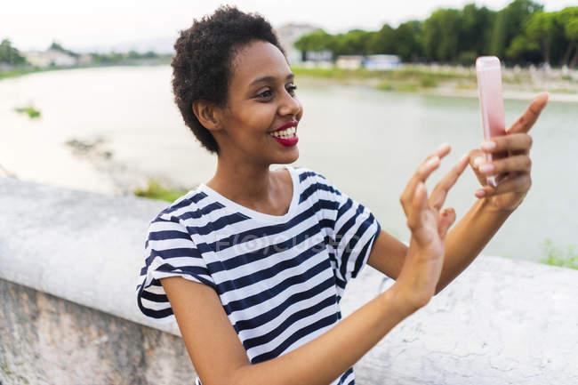 Souriant jeune femme utilisant un téléphone cellulaire au bord de la rivière — Photo de stock