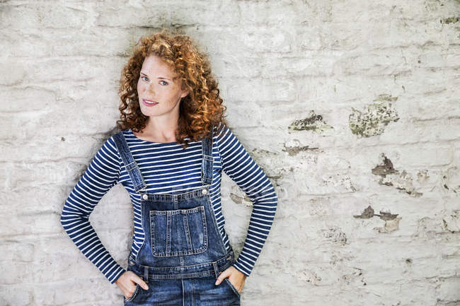 Portrait of smiling young woman wearing denim dungarees leaning against white brick wall — Stock Photo