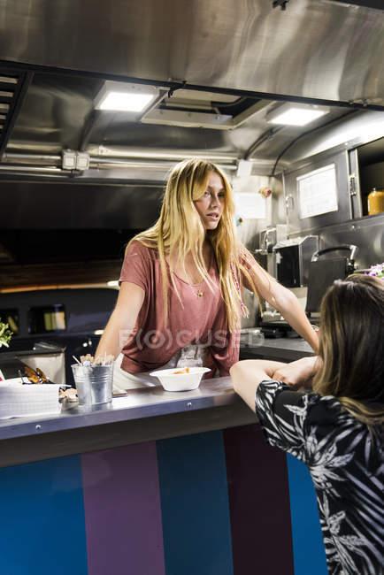 Mujer joven en un camión de comida hablando con el cliente - foto de stock
