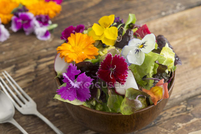 Bowl of salad with edible flowers — Stock Photo